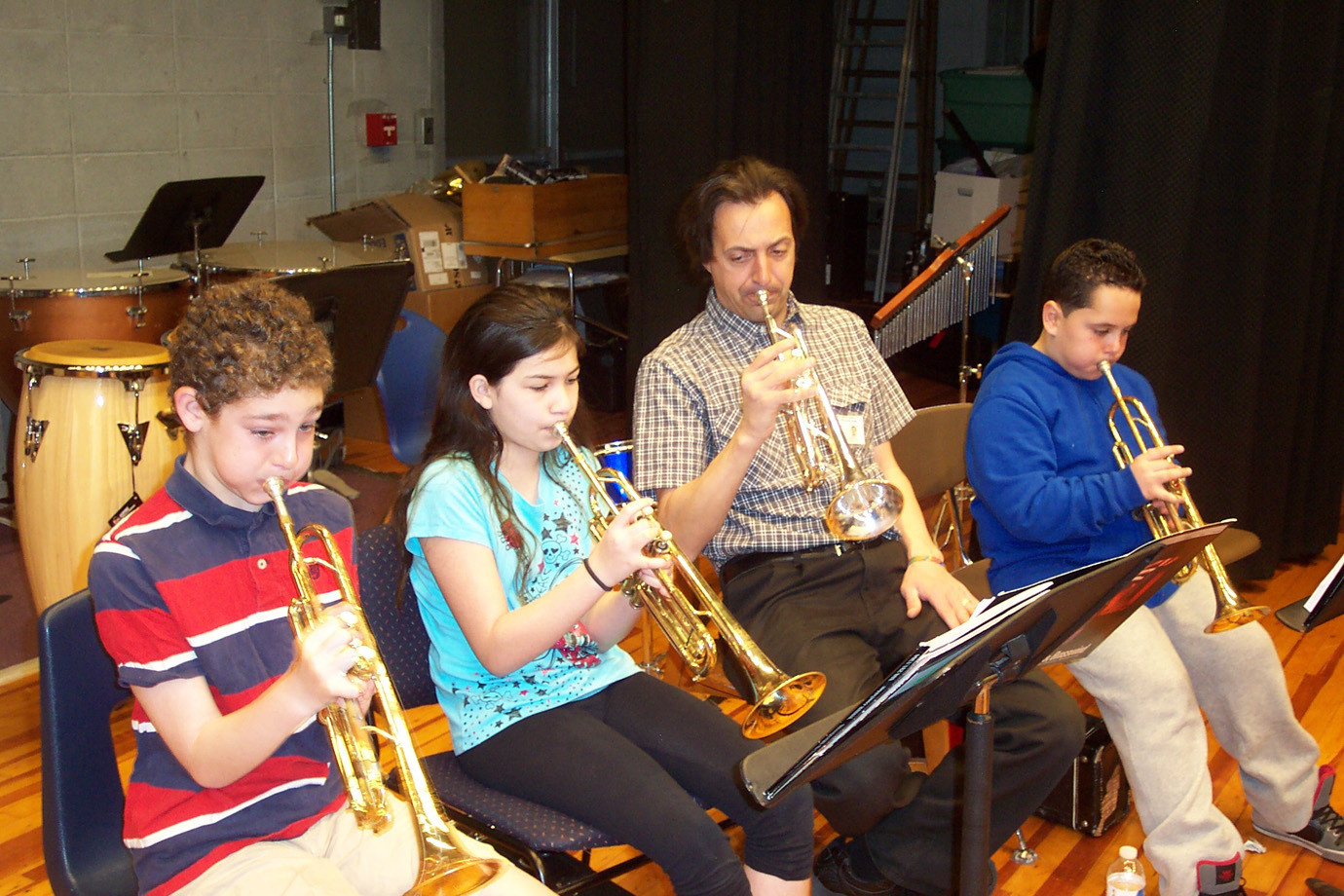 "Band Director Mario Blanco is shown here helping fifth graders Joshua Winderman, Emily Steel, and Nicholas Giorlando rehearse the trumpet sections of  ""Dragon Slayer."""