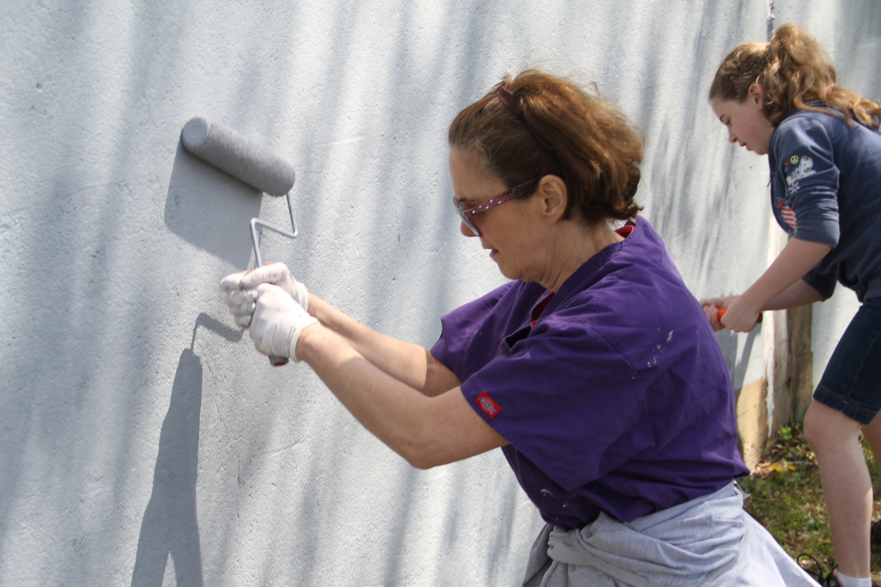 Debbie Laskin and Erin Laxton were among the many volunteers from Envision Valley Stream who painted the Long Island Rail Road trestle wall on April 28.