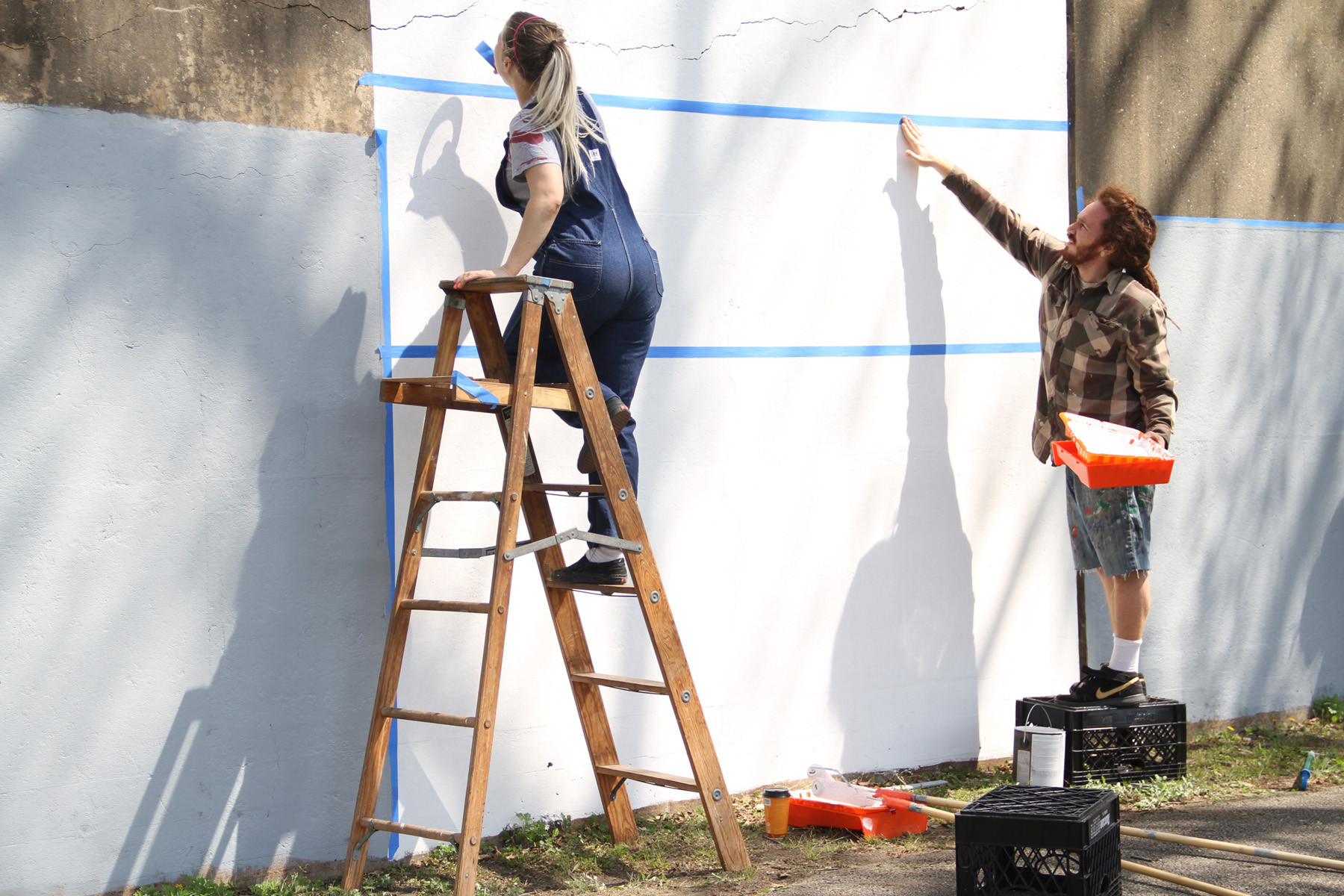 Artists Brittany Ruhnke and Christopher Berger prepared the trestle wall for the mural.