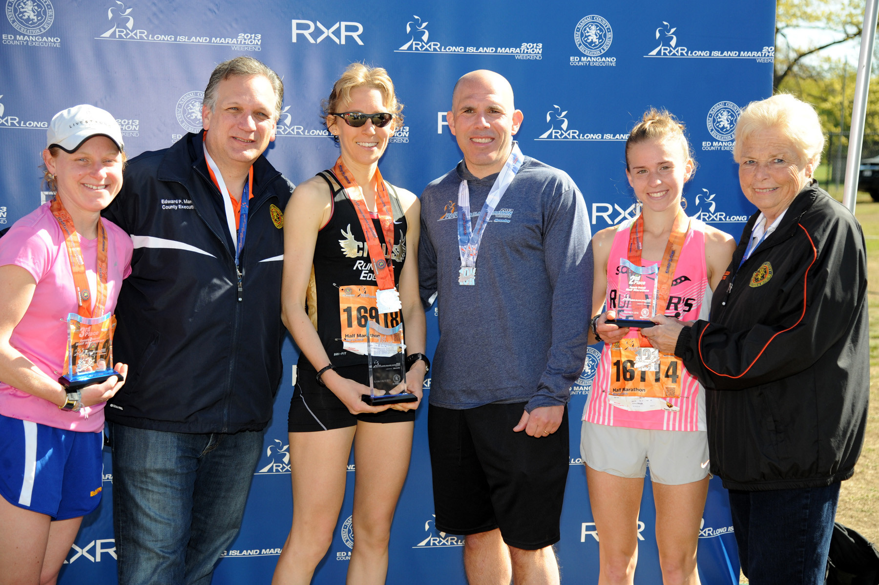 County Executive Ed Mangano, second from left, and Scott Rechler, CEO of RXR realty, the race's title sponsor, with the women's top three half marathon finishers, first-place Jodie Robertson, third from left, second-place Stefanie Braun, second from right, and third-place Lindsey Block, far left. Also pictured is County Legislator Rose Walker.