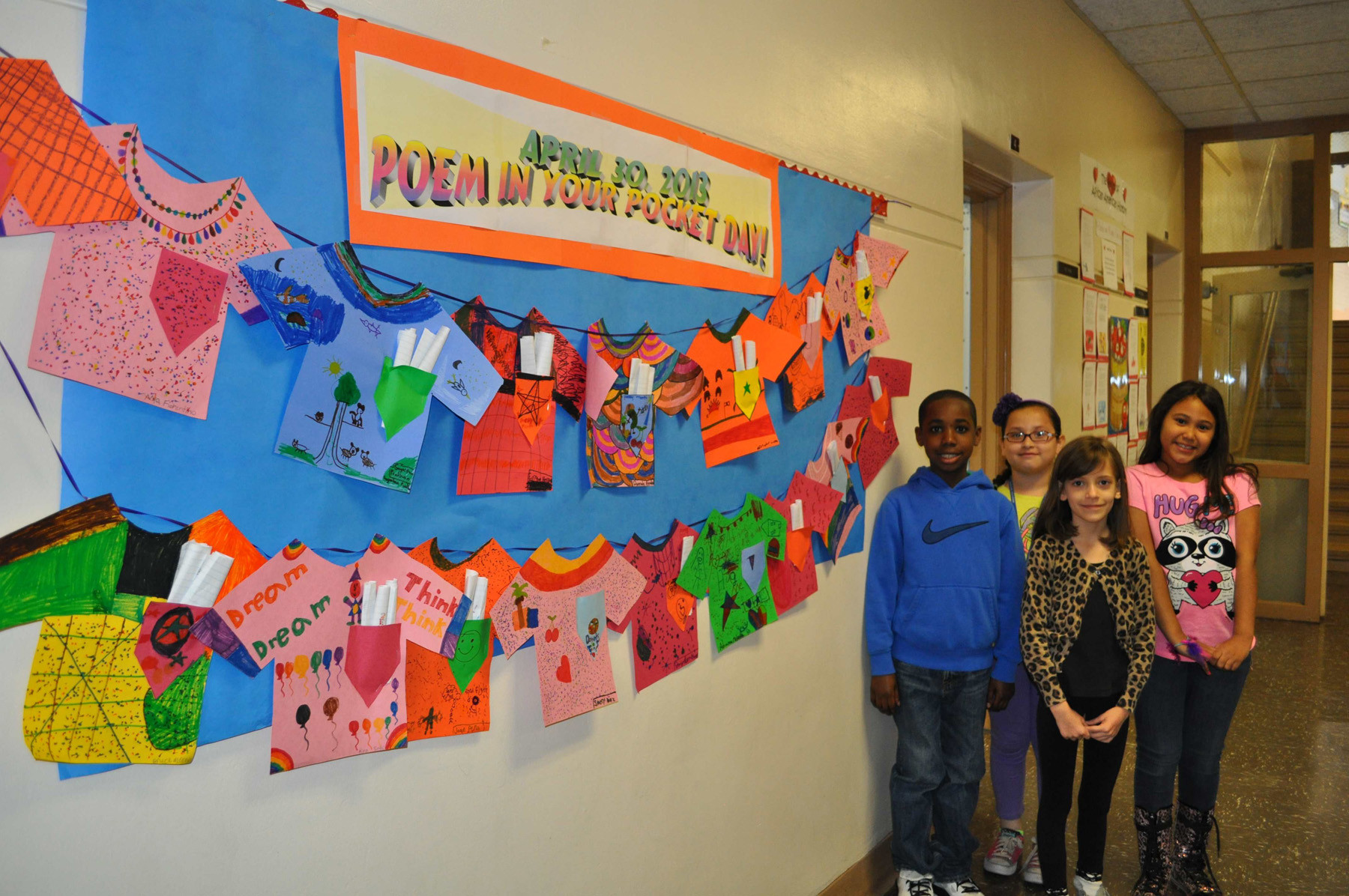 "Third-graders Jayden Chang, left, Dannah Ayala, Veronica Beach and Mya Fiorentino wrote poems and put them in a specially created ""pocket"" on their class' bulletin board."