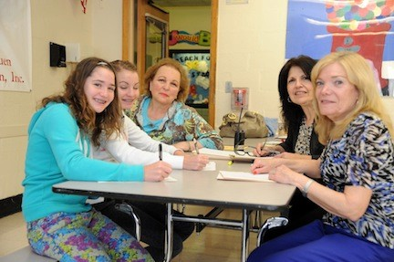 Twins Corrine and Chloe Morales, 13, signed up for their heart screenings with help from organizer Susan Gruen Helsinger, left rear, and Central District secretaries Cathy Paolillo and Alberta Miller.