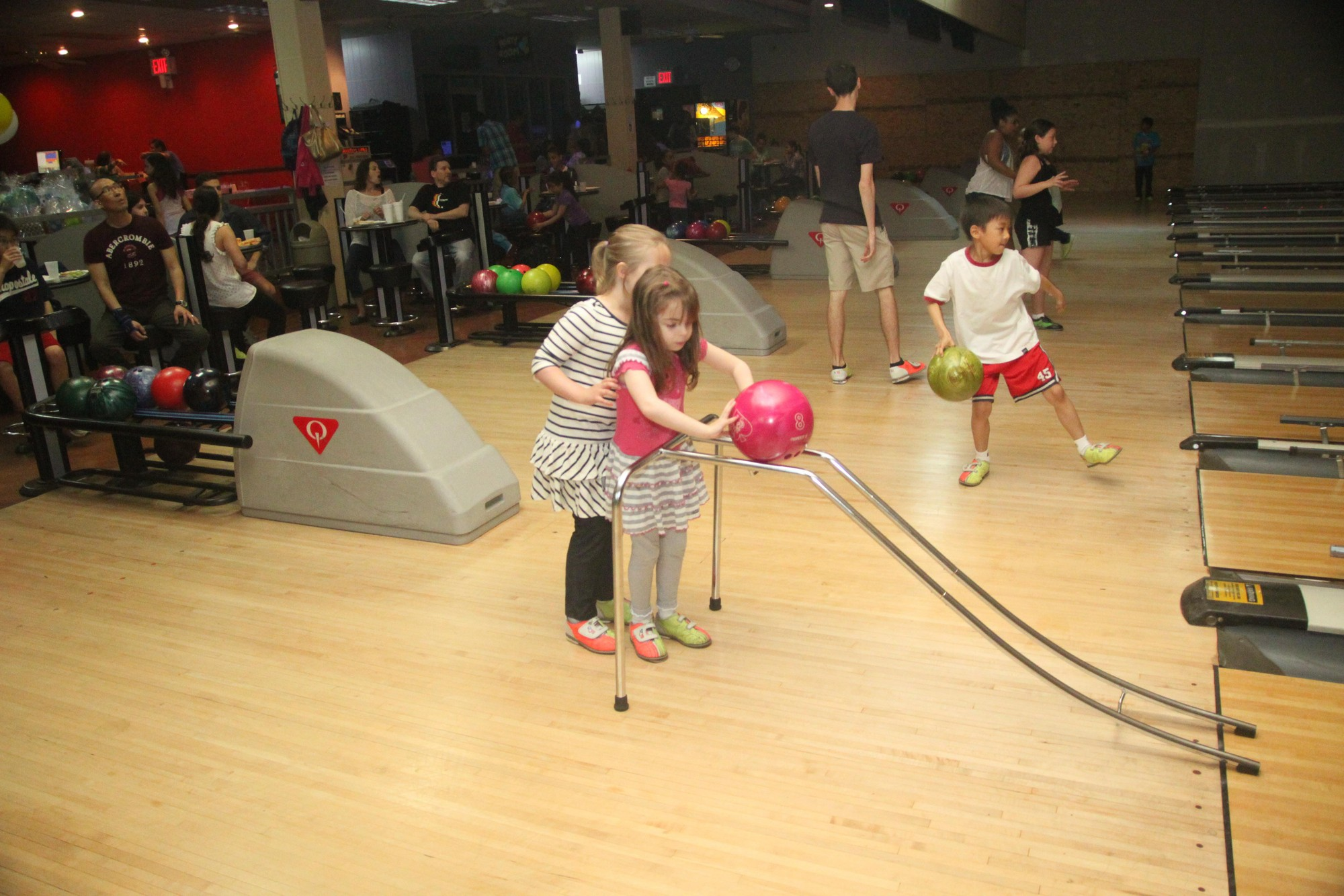 SIBSPlace supports children whose parent or sibling is suffering from cancer or another devastating illness. Erin Khankan, 7, left, helped Charlotte Formont, 5, set up to roll the bowling ball down the lane.