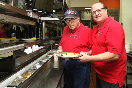 Community Chest President Eric Keslowitz, right, and his father, Bernard, help out at the Flapjack Breakfast.