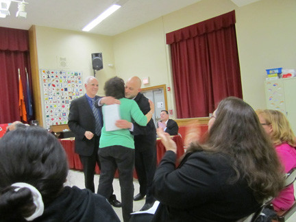 Michele Meehan, a special-education aide at Old Mill Road School, received a hug from John McDaid, the Old Mill Road principal, at the May 14 North Merrick Board of Education meeting as he presented her with a certificate of recognition and appreciation for using the Heimlich maneuver to save a student from 