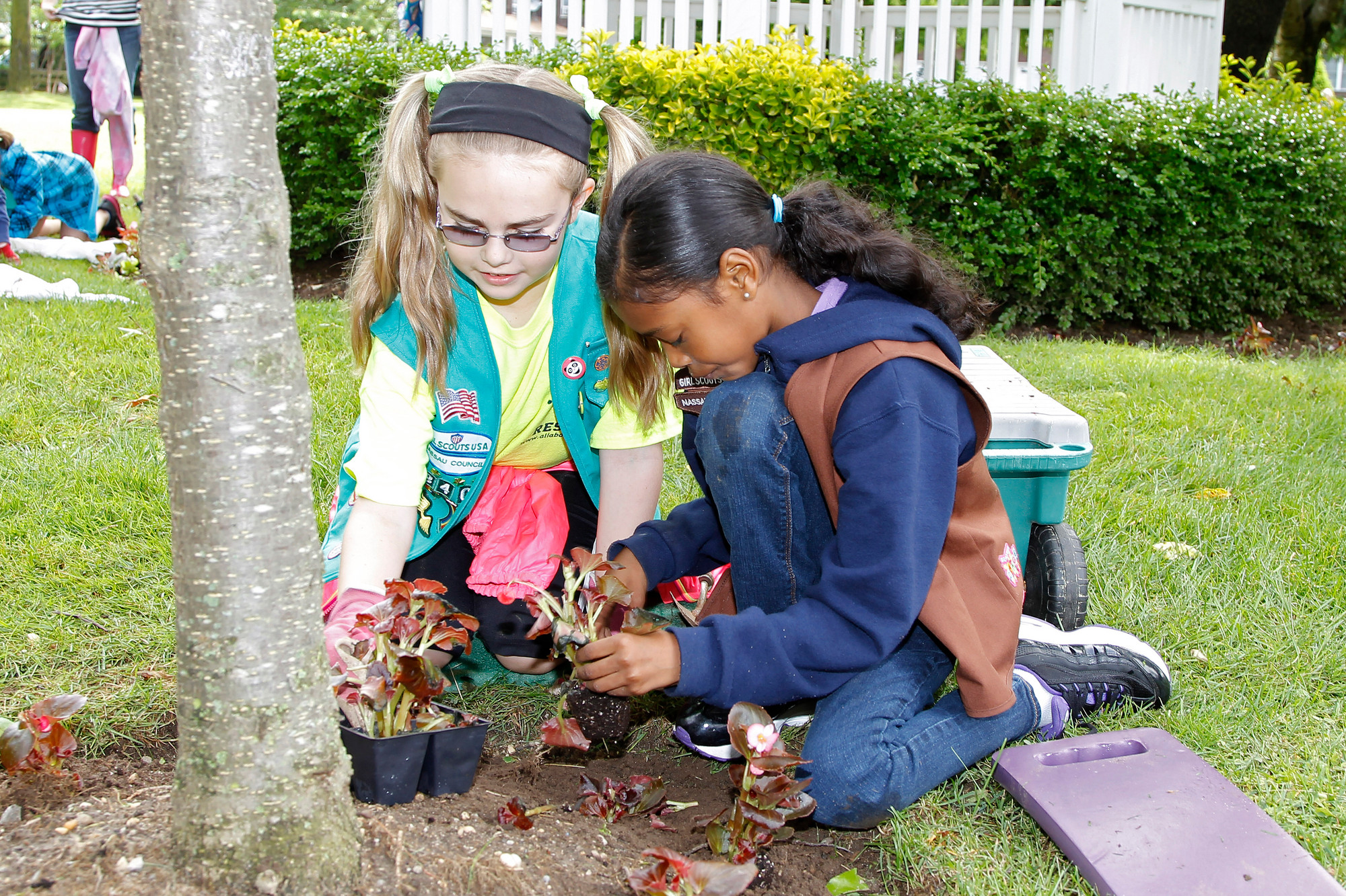 10-year old Catherine Farrell, left, from Troop 840, and 8-year-old Damaris Linsay, from Troop 814, were hard at work putting in plants for the Village Green beautification project.