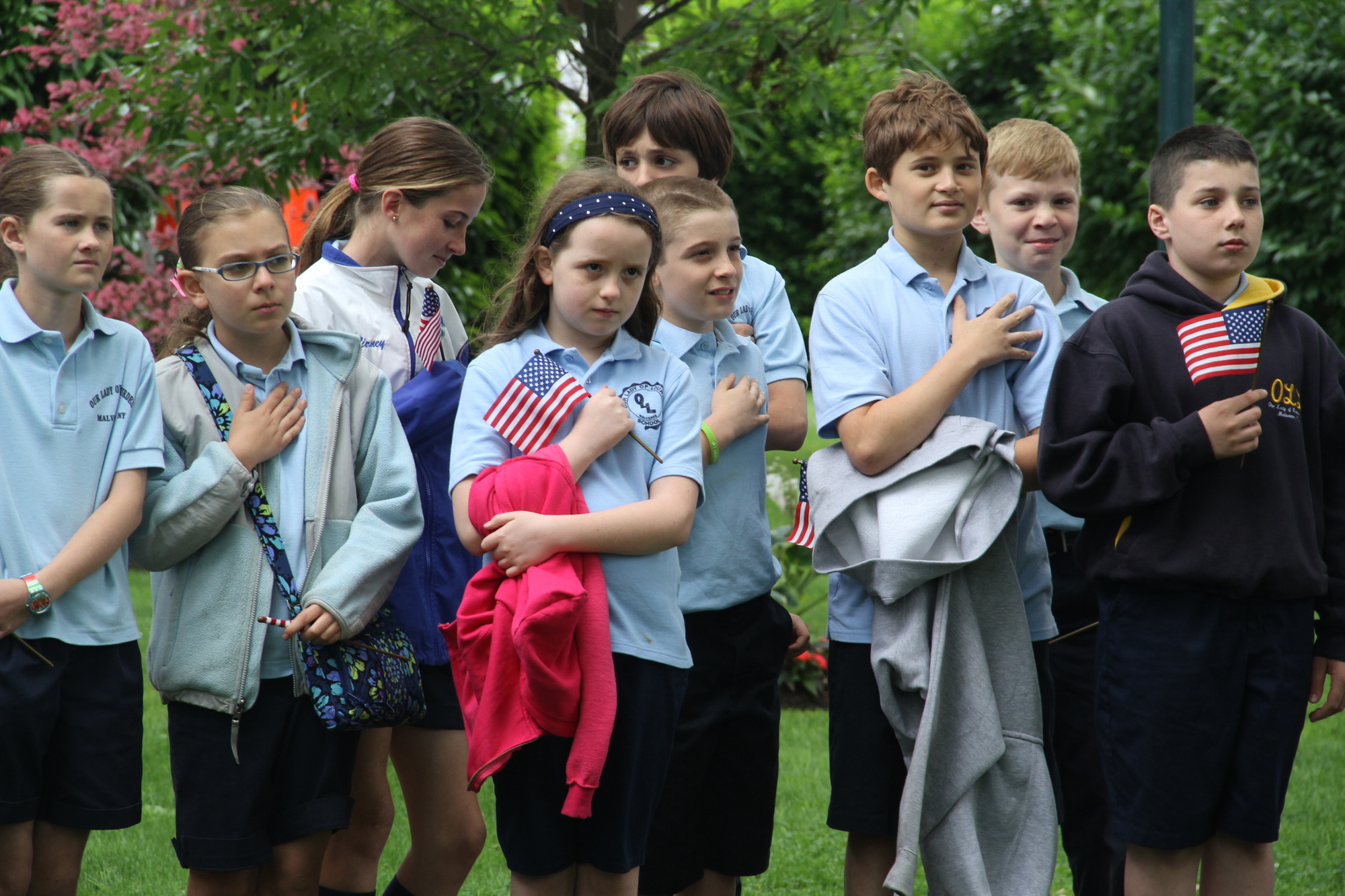 Fifth grade students from Our Lady of Lourdes School listen to the National Anthem. Residents, students and their families gathered at the gazebo in Malverne to celebrate Flag Day.