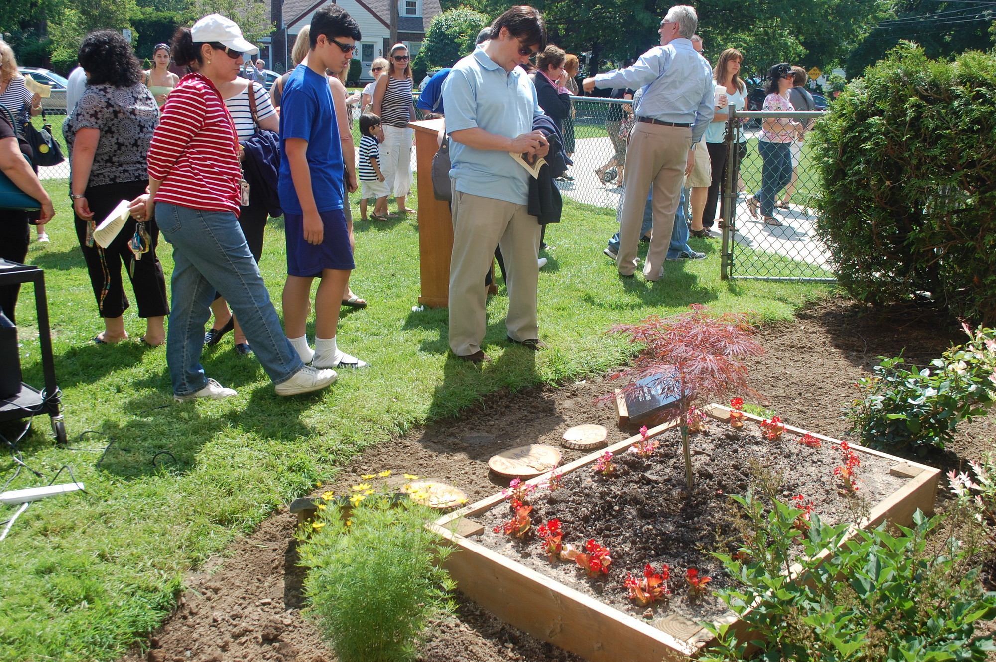 Guests at last Saturday morning's ceremony look over the garden built outside of Memorial Junior High School in honor of former teacher Stephanie Ginsberg.