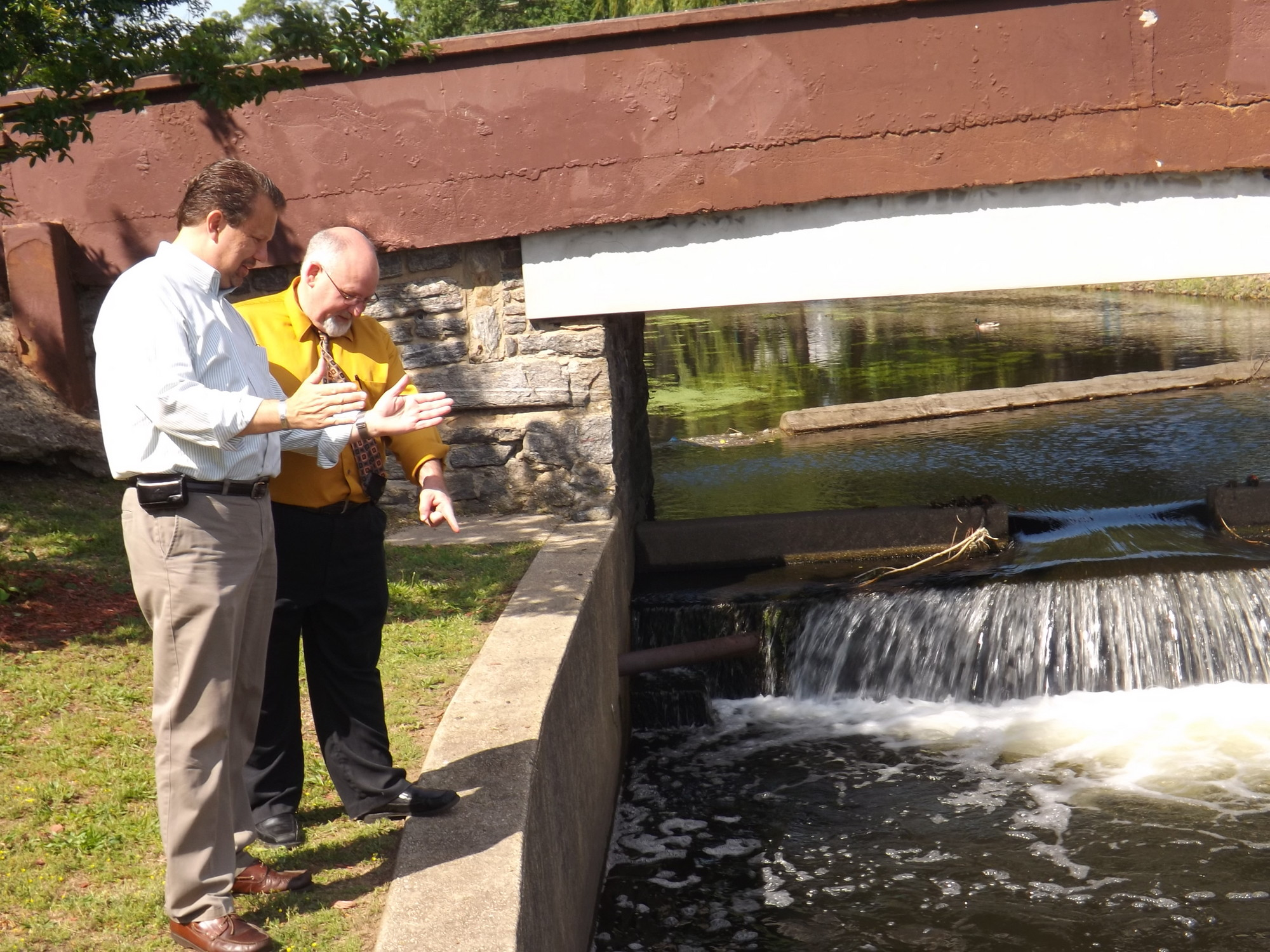 Mayor Ed Fare, left, and Deputy Village Clerk Rich DeAngelis checked out the carp at the lake in Hendrickson Park. The village will host a free family fishing weekend on June 29 and 30.
