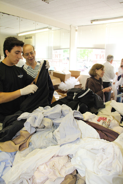 Neil Krenik, right, assisted by Giovanni Girardi of Jim Dandy Cleaners, was one of many who returned to Lewis Cleaners to find their lost clothes.