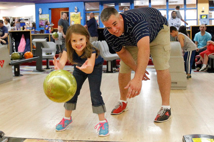 Five-year-old Emily Coyle, coached by her uncle Kevin Kyrillidis, was all smiles as she sent the ball down the alley.