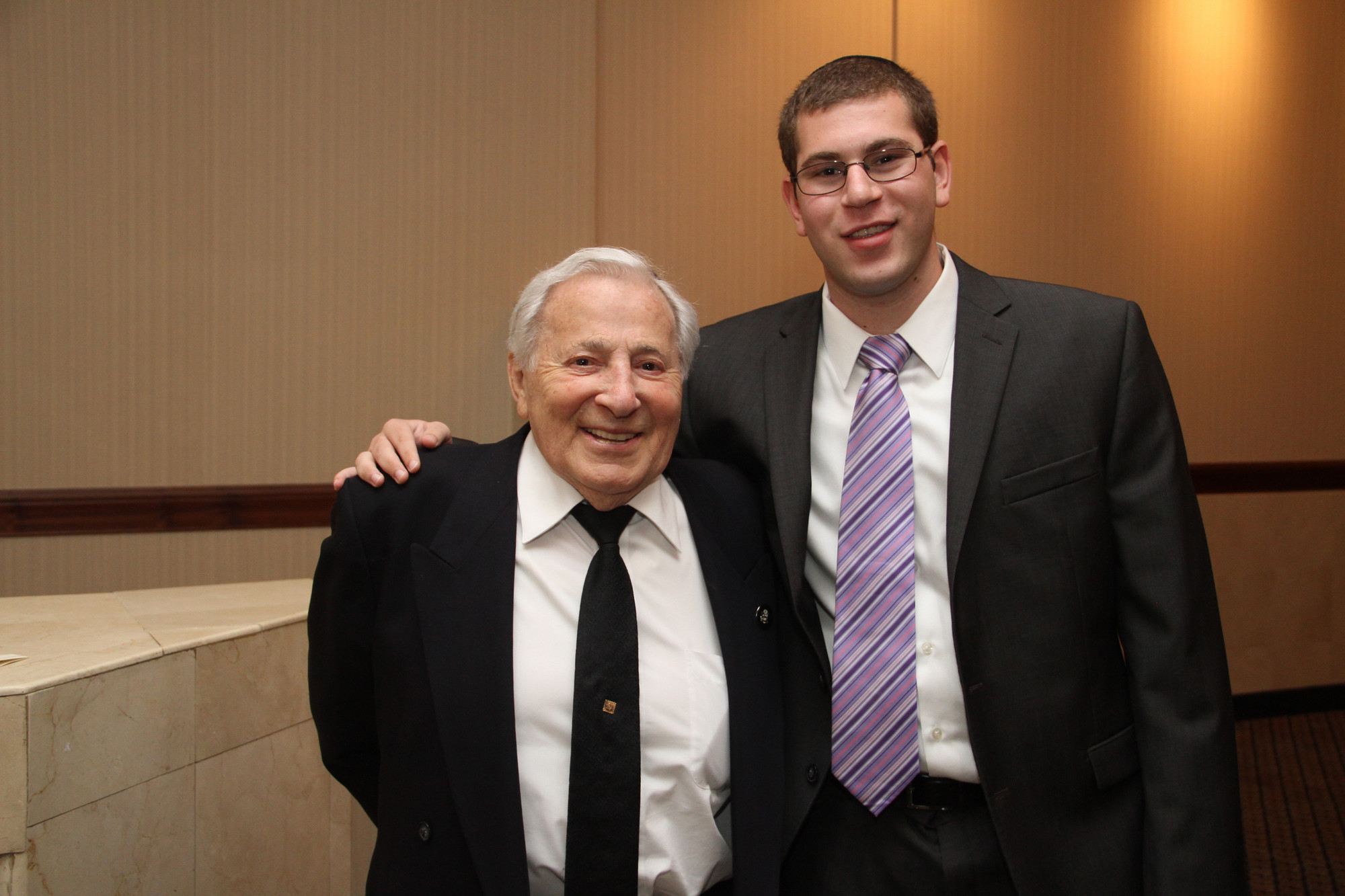 "Rambam Mesitva in Lawrence presented an honorary high school diploma to Holocaust survivor Jack Ratz, left, who ""graduated"" with his grandson Brian Fine."