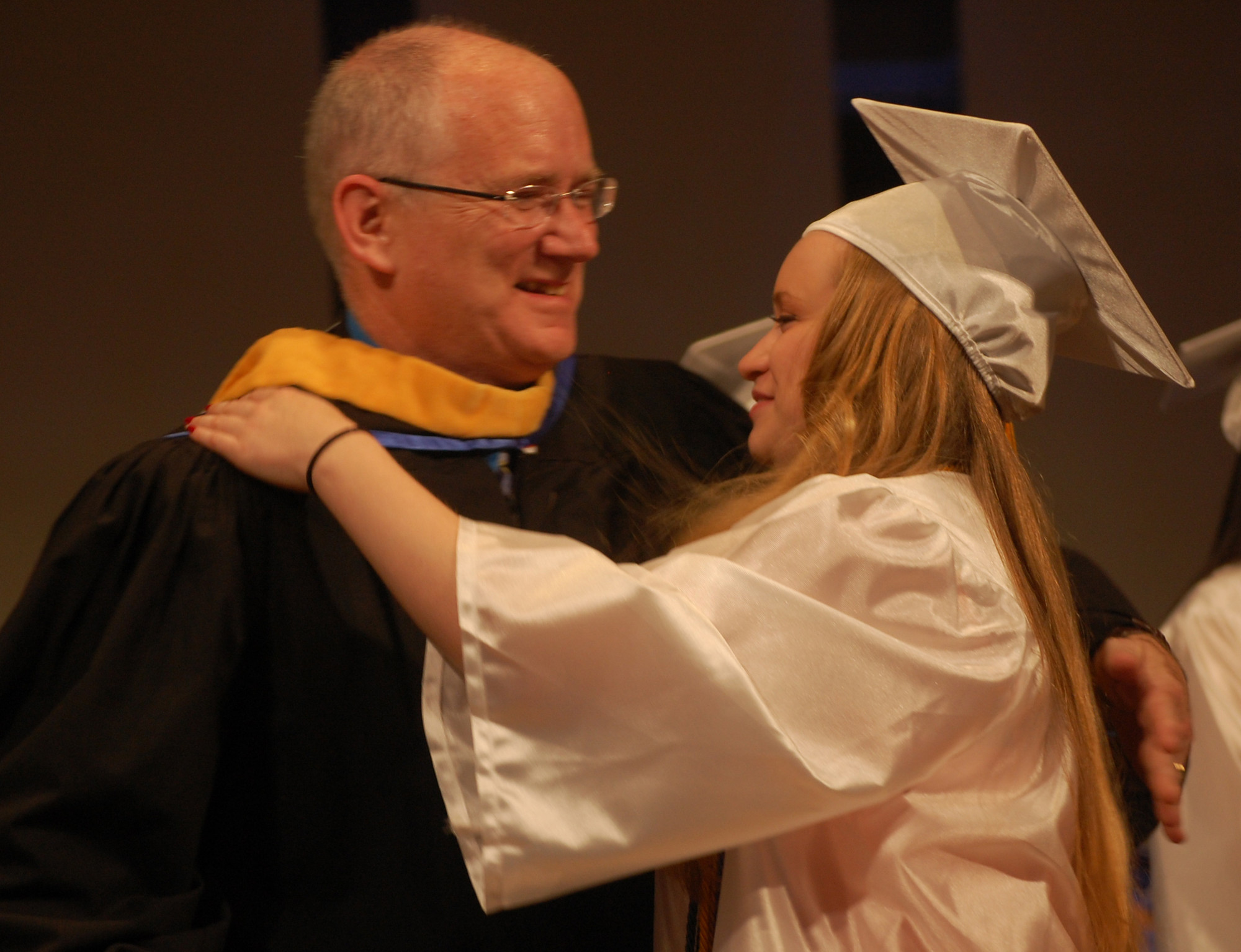 Board of Education Trustee Ken Cummings presented his daughter, Colleen, with her diploma on June 19. Her twin sister, Julia, followed her across the stage.