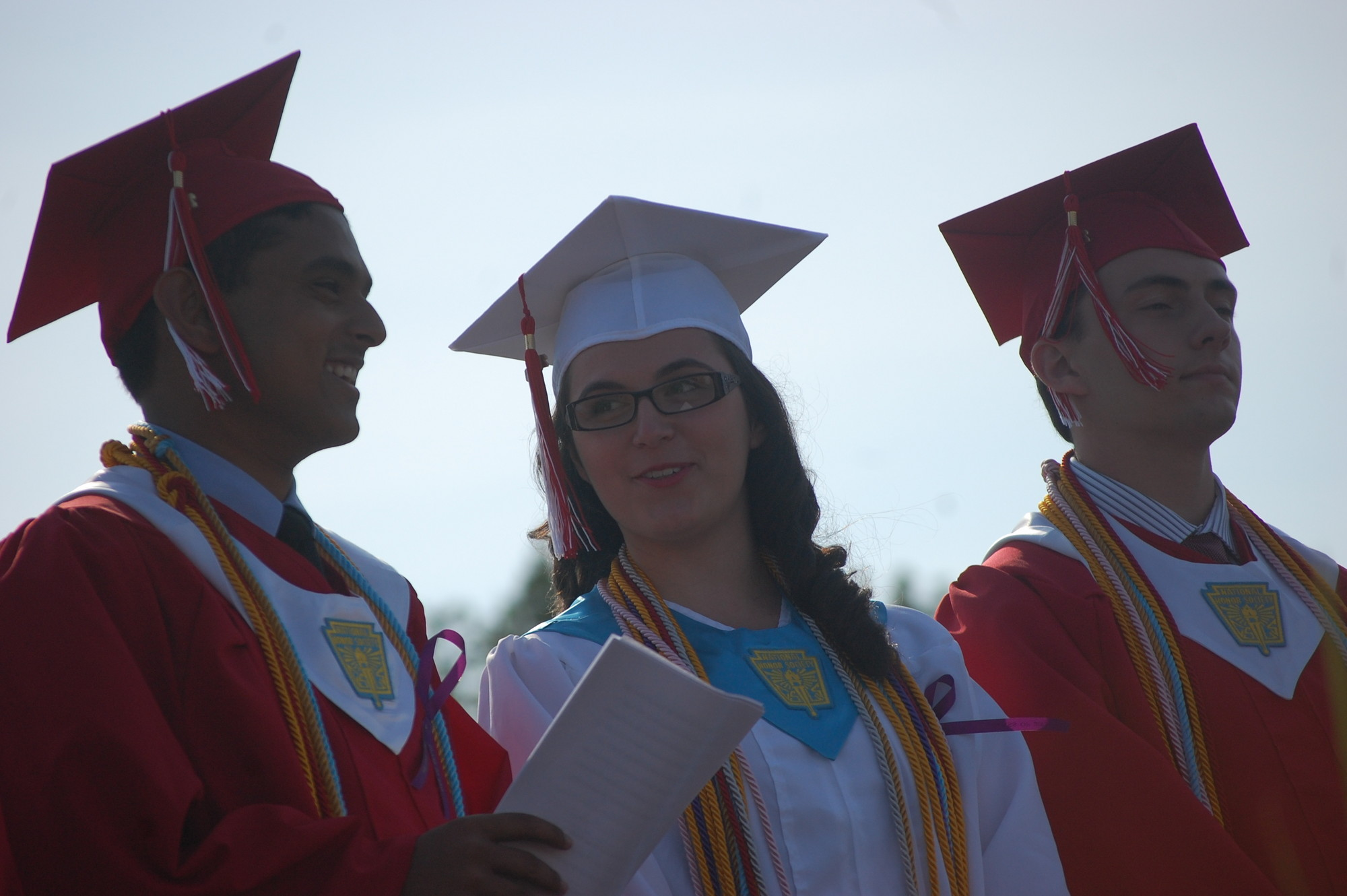 Class President Nihal Majumder, salutatorian Jeanne Powell and valedictorian Andrew Hess watch their fellow graduates arrive.
