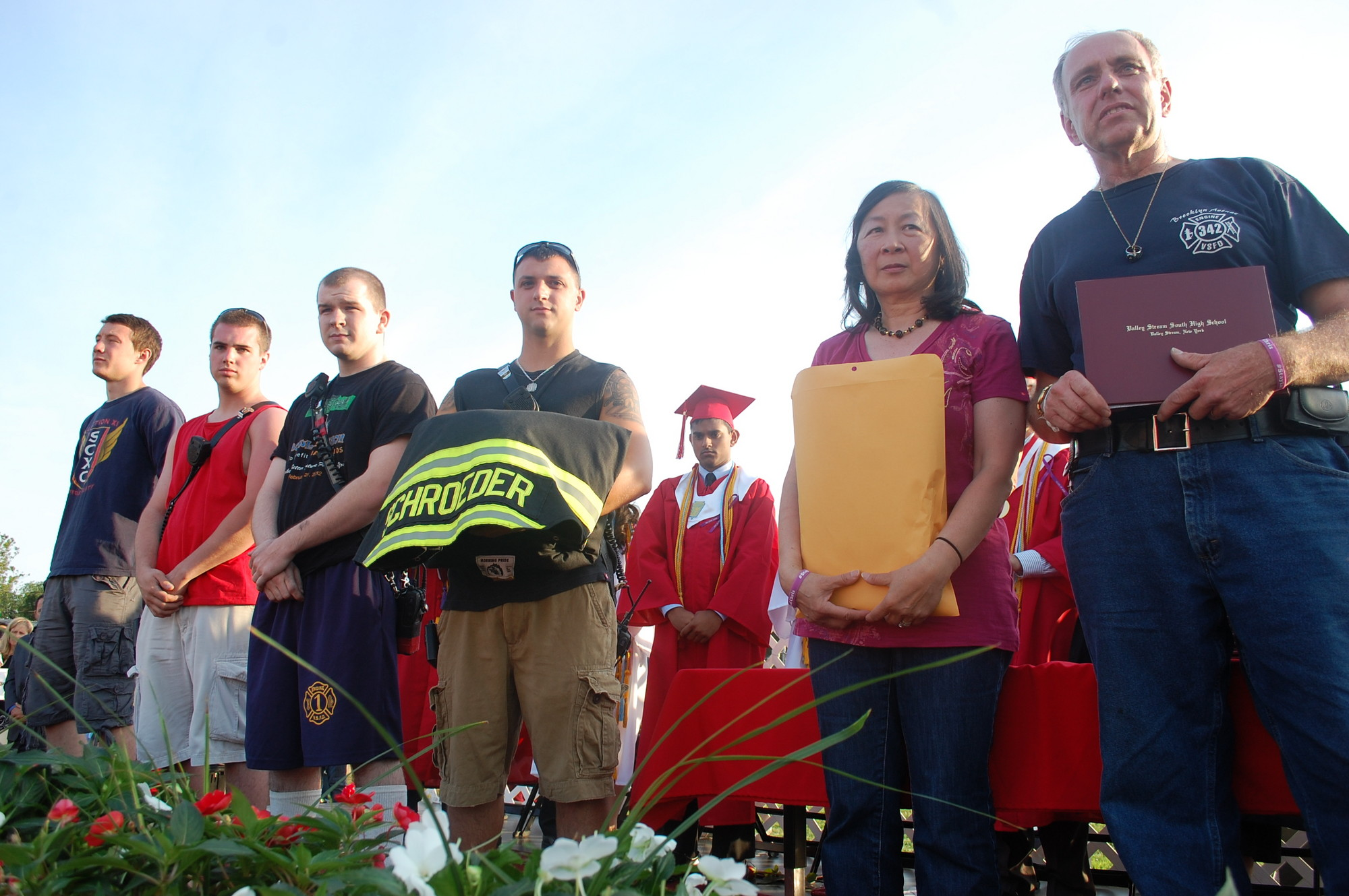 Members of the Valley Stream Fire Department joined Carole and Wally Schroeder on stage who were presented with a diploma for their son, Chris.