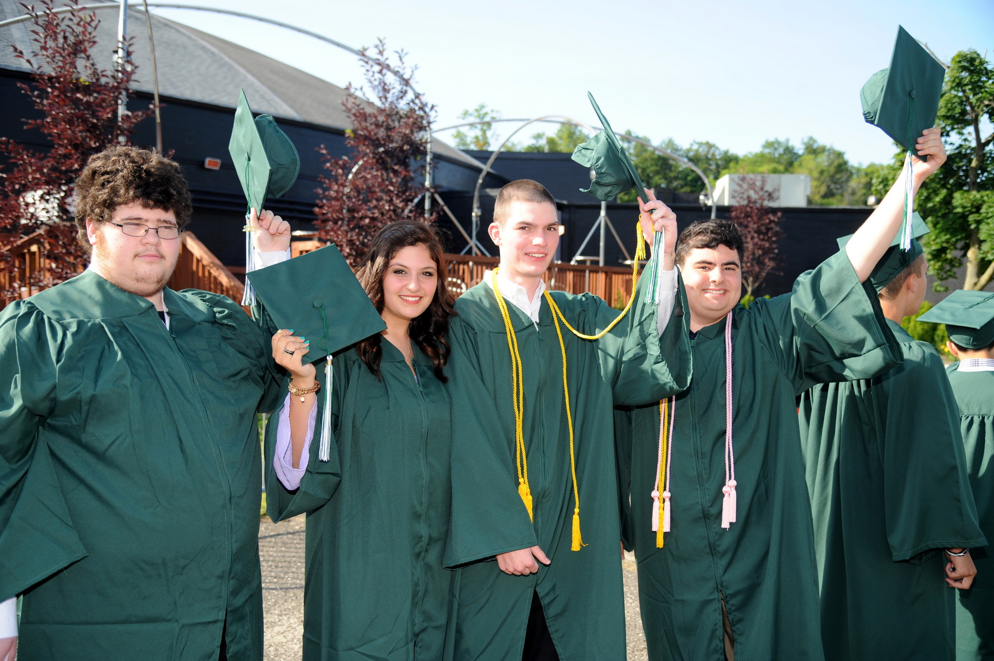 Kennedy students Kyle Freedman, Jhanna Firestone, Andrew Field and Alec Ferretti doffed their graduation caps Sunday outside the NYCB Theater in Westbury.
