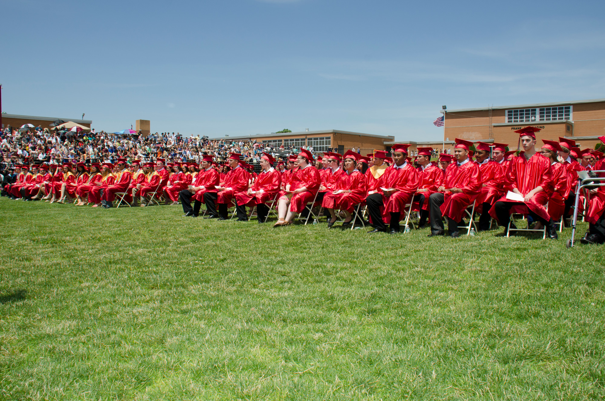 The graduating seniors lined the field under sunny skies, surrounded by their friends and family members in the bleachers.