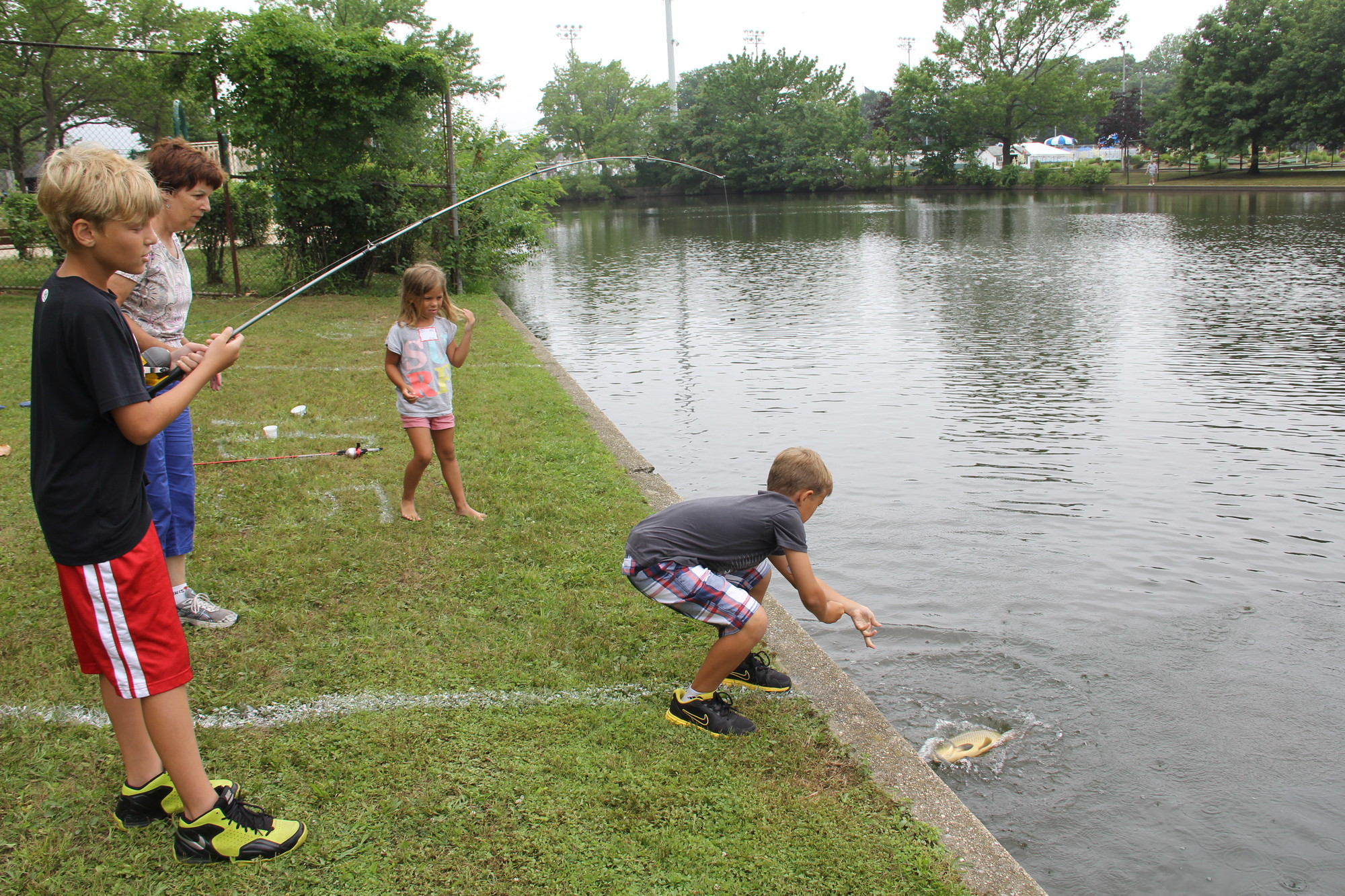 Jesper Dalessandro, 11, reeled in a large bass while his brother Tyler, 9, helped pull it from the water, as their grandmother, Sue, and sister, Molly, 7, watched.