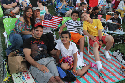 The Cintron family waved the American flag as they laid out on park grass.