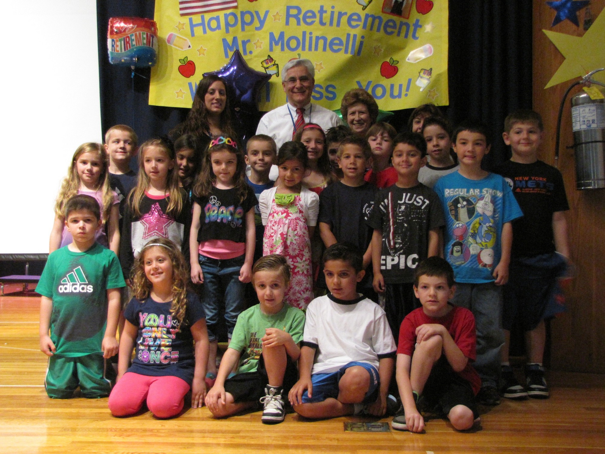 Charles A. Reinhard Early Childhood Center Principal Clifford Molinelli, center, and his wife, Antoinette, with first-grade teacher Lauren Giordano, her class and the entire student body at a special assembly held in Molinelli�s honor.