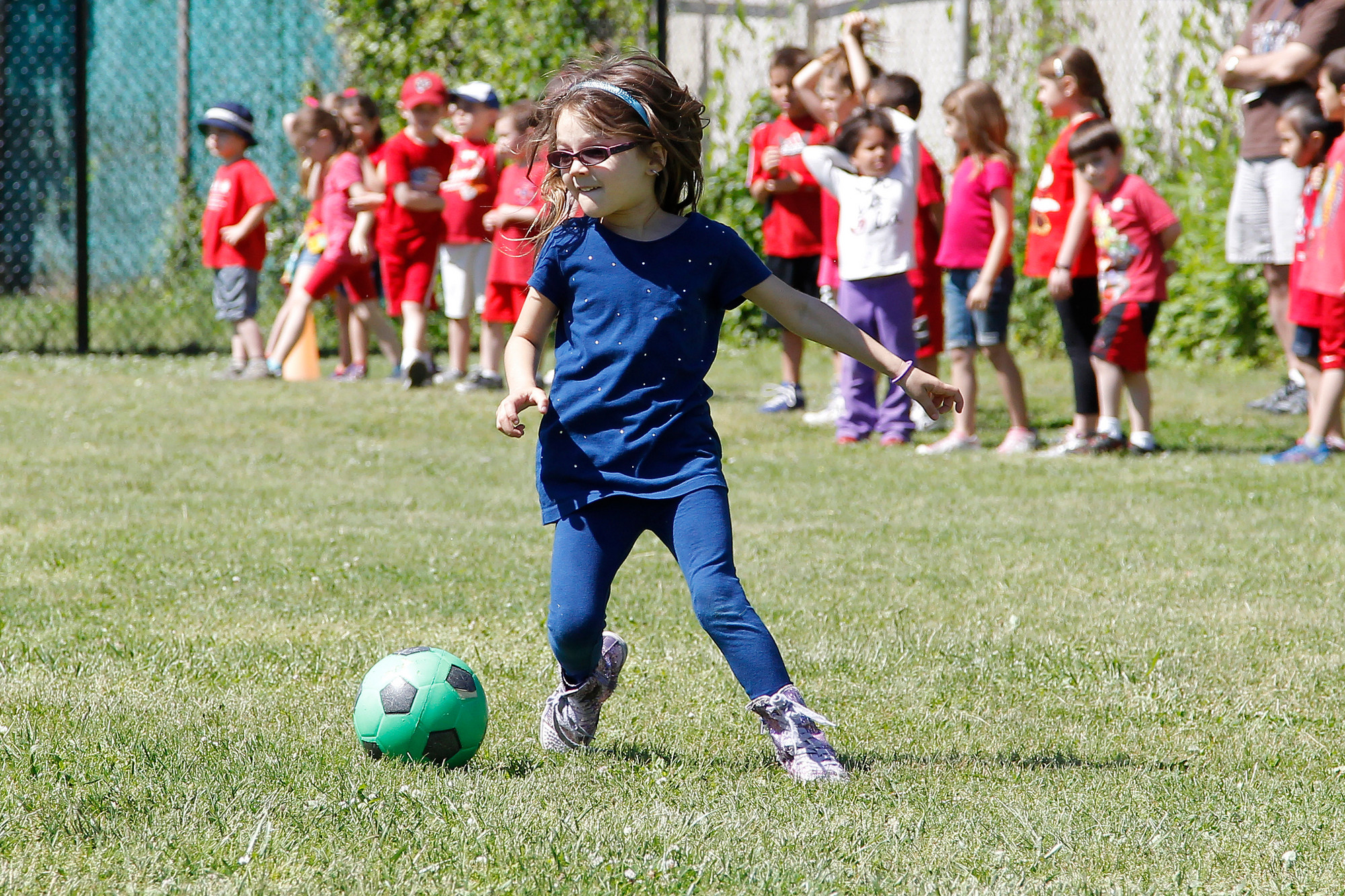 Kindergartner Cadence Anofossi kicked the soccer ball for the blue team as she made her way to the finish line.