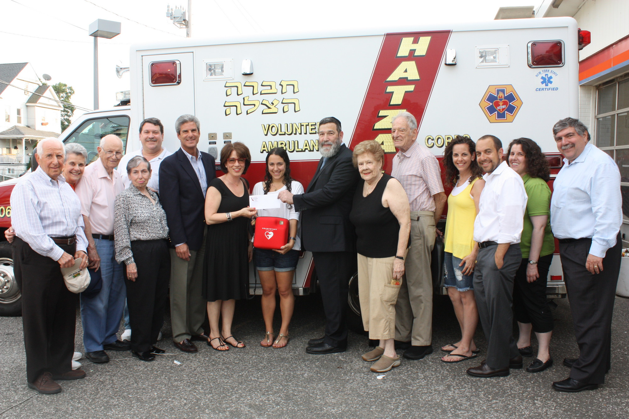 Five Towns Community Chest raised $1,800 to buy an automated external defibrillator and donated it to Hatzalah in memory of Wooodmere resident Eric Matza. Arielle Matza, Matza's daughter, held the AED.