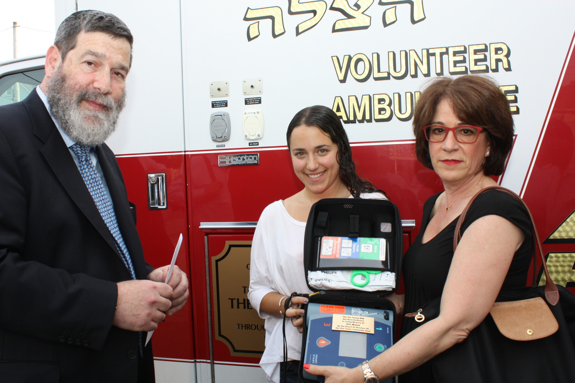 At the dedication ceremony, Robin Matza displayed the AED kit. At left Hatzalah coordinator Rabbi Elozer Kanner and Matza's daughter, Arielle.