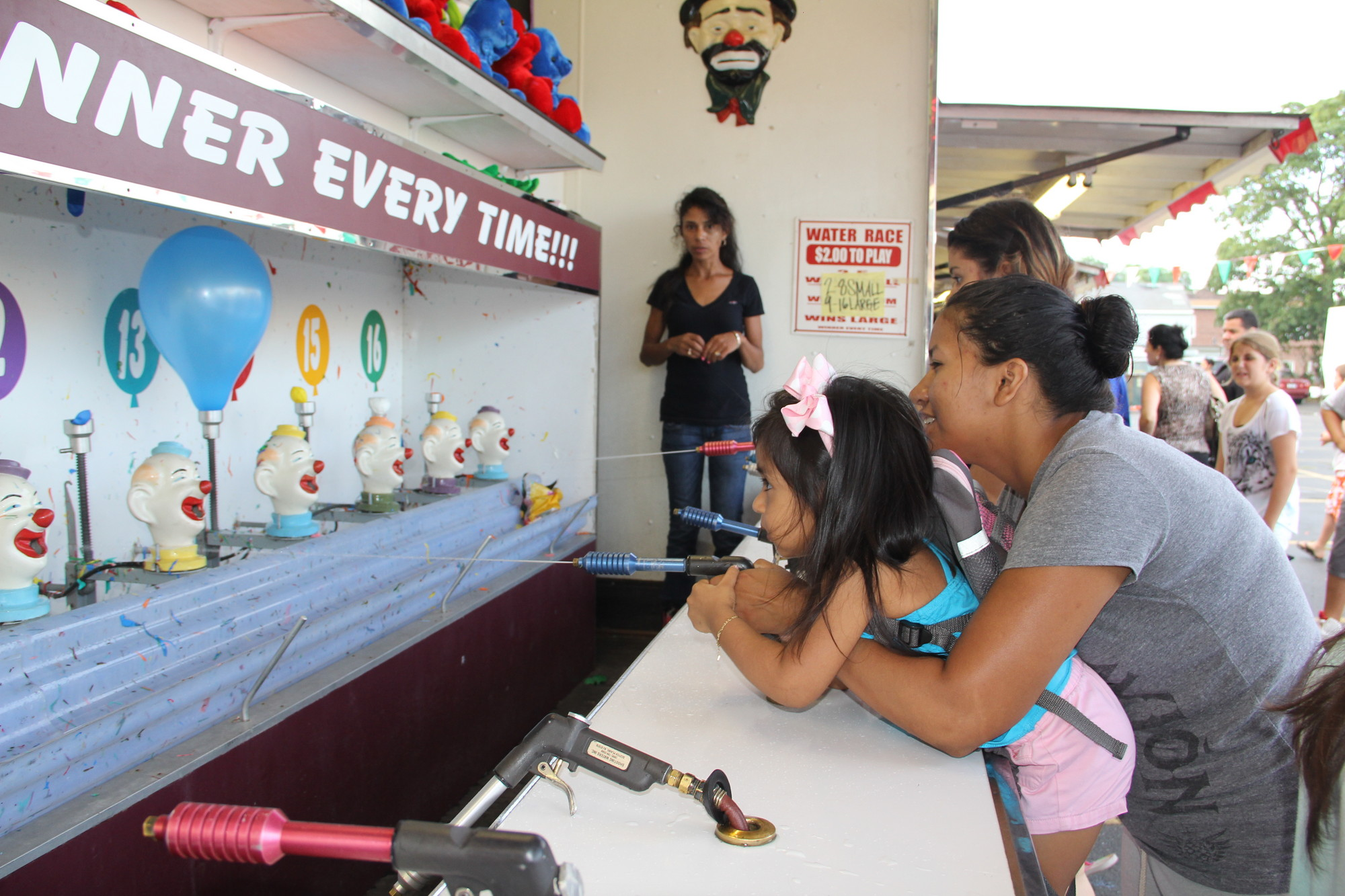 Family fun at the Santa Marina Feast. Kaoma Canales helped her daughter,  Mayra, fill up the balloon with water.