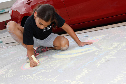 Nicole Cataleo, of East Rockaway, got down and dirty to draw her picture on the sidewalk outside Village Hall.