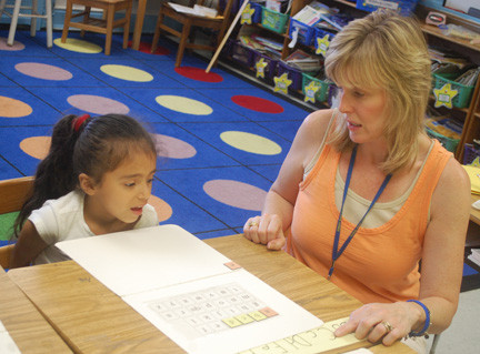 Kim Lapera works with Melissa Alvarenga on her reading skills.