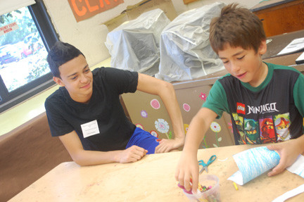 Brian Bauman, a volunteer with District 13's summer recreation program, watches Anthony Duran work on his arts and craft project.