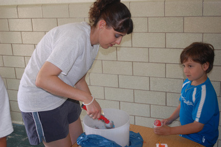 On a very hot day, counselor Missy Levison helped Ethan Rivademeria cool off by serving him an Italian ice.