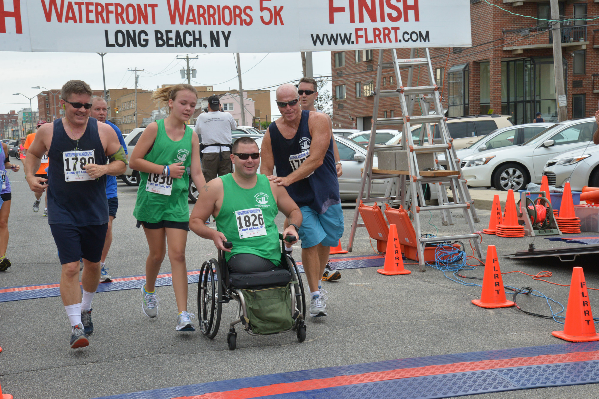 Robbie Michaels, left, Katelyn and John Hayes, and Long Beach Waterfront Warriors Co-Chair Jerry Snell crossed the finish line during the Waterfront Warriors annual 5K race in the West End.