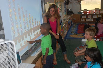 Jessica Correale, a volunteer with the District 24 summer school and an aspiring teacher, helps kindergarten students with their math skills.