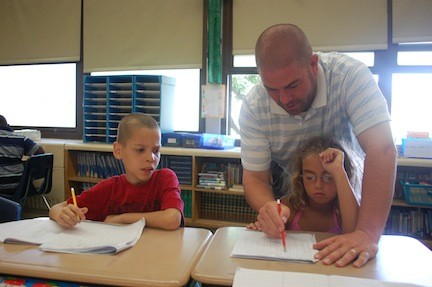 Teacher John Reece reviews times tables with students in his class.