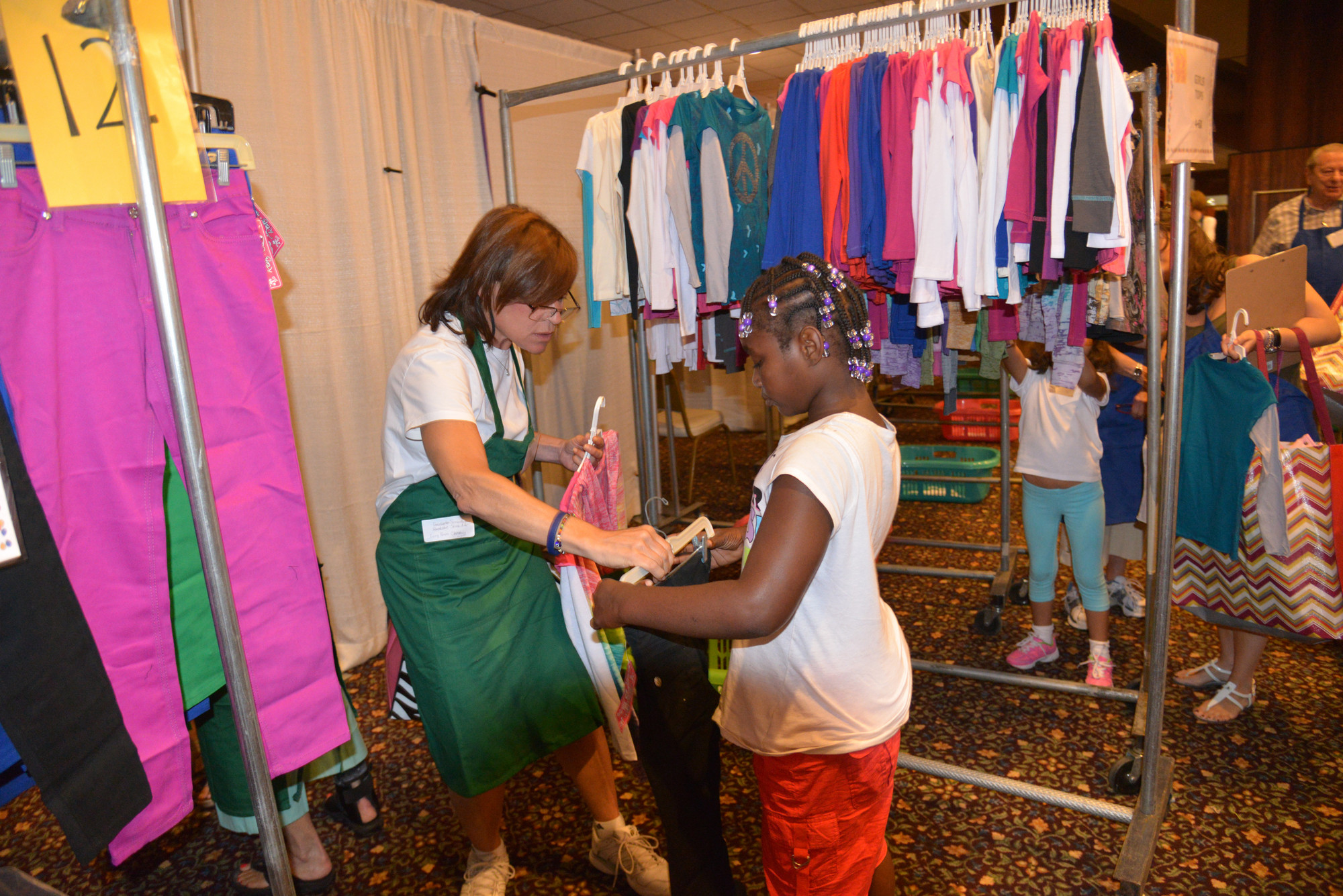 Donna Zides helped Samantha Stockdale pick out pants at the NCJW back to school store.