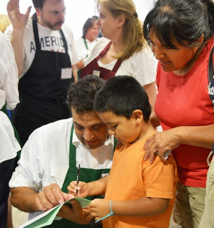 NEIL SKLAR helped Danilo Bustillo check off the school supplies he needs as mom Romula Cuba watched.