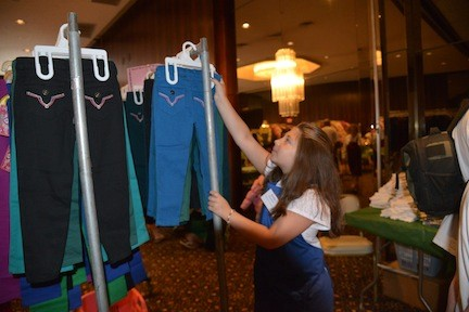 junior volunteer Emily Rosenblum, 9, helped organize pants at the back to school store.