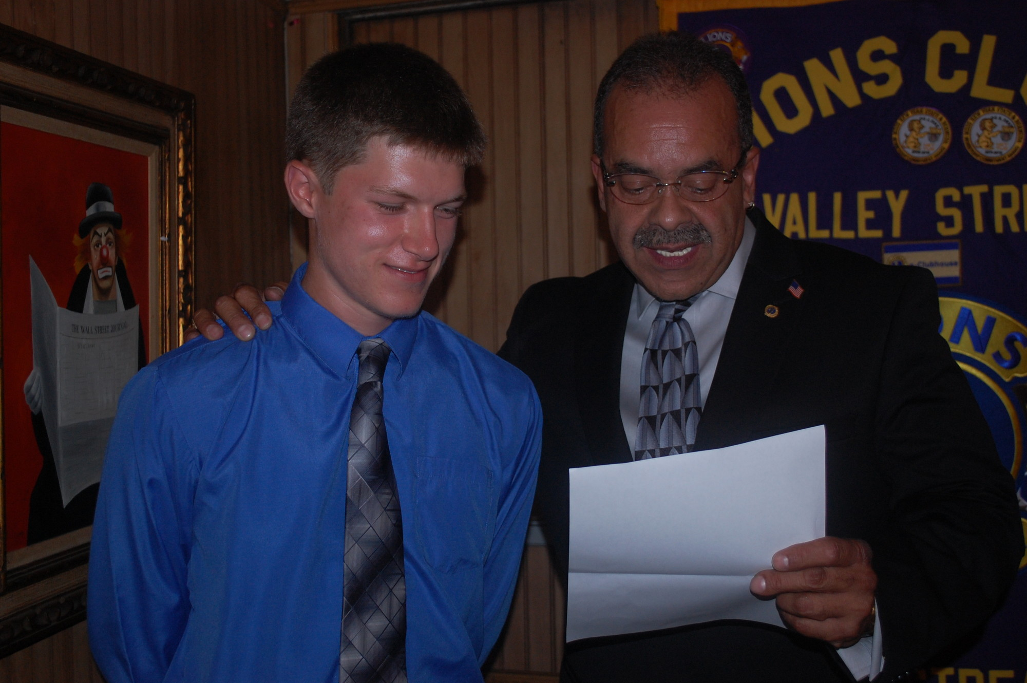 David Meltzer, left, listened as Valley Stream Lions Club President Jose Pastrana talked about the organization's scholarship program on Aug. 7. Meltzer went home with $1,000 for college expenses.