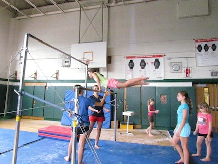 Students practiced the uneven bars during gymnastics class.