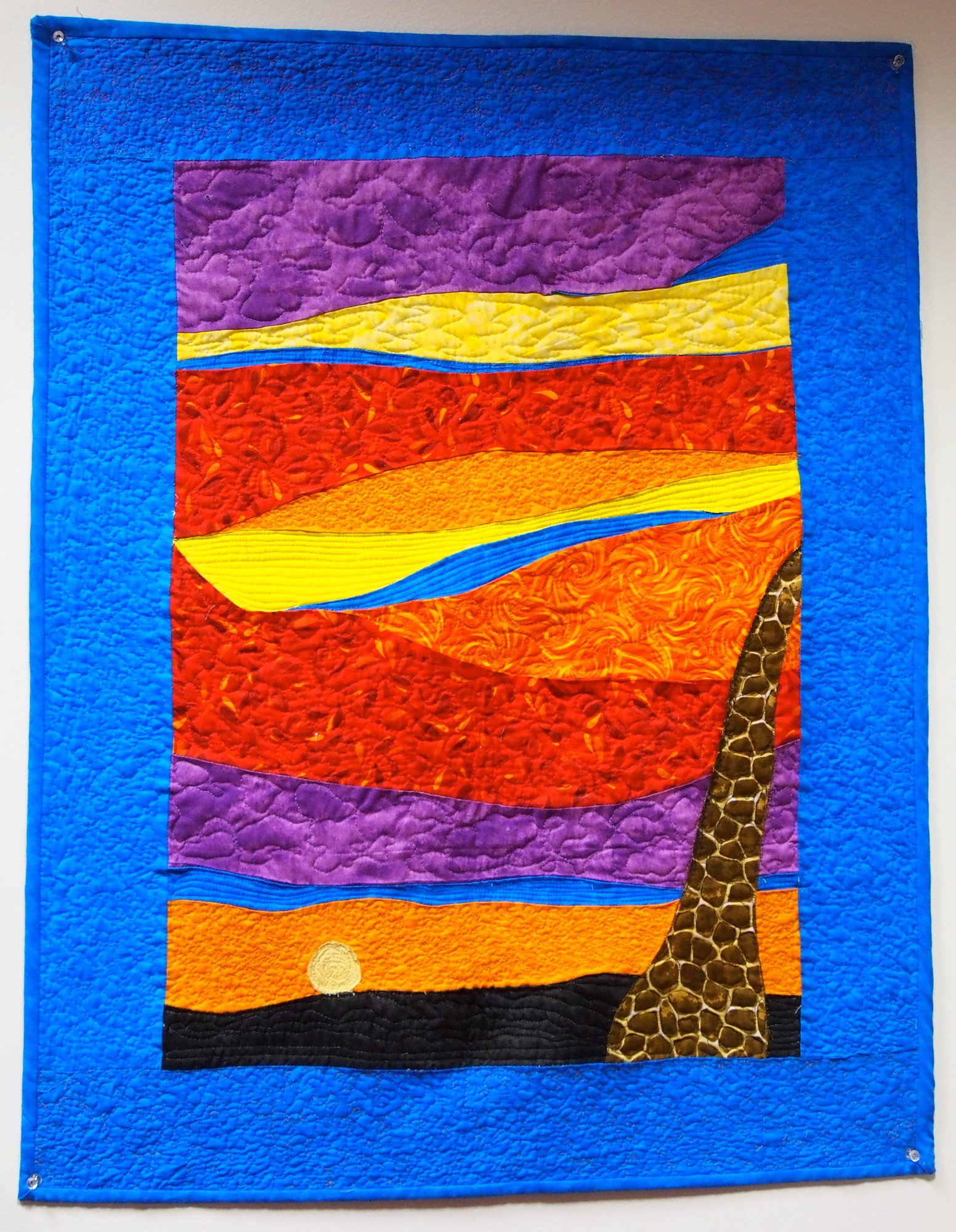 This quilt, Sunset on the Serengeti, was inspired by a conversation with the artist's daughter. The discussion was about clashing colors and how hues that don't complement one another in fashion often do so in nature.