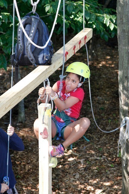 Gisele Cruz, 8, climbed a post to retrieve a backpack that her team needed during the Olympics.