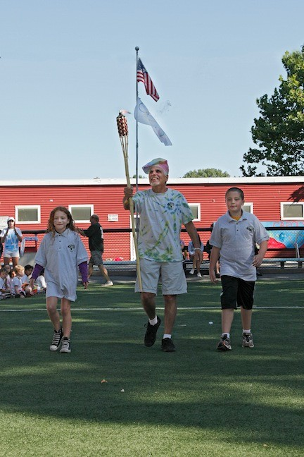 "Steve Meltzer, center, accompanied by ""camp mayors"" Haley Hepworth, 7, and Andrew Shea, 10, carried in a torch at the start of the Olympics-themed competition."