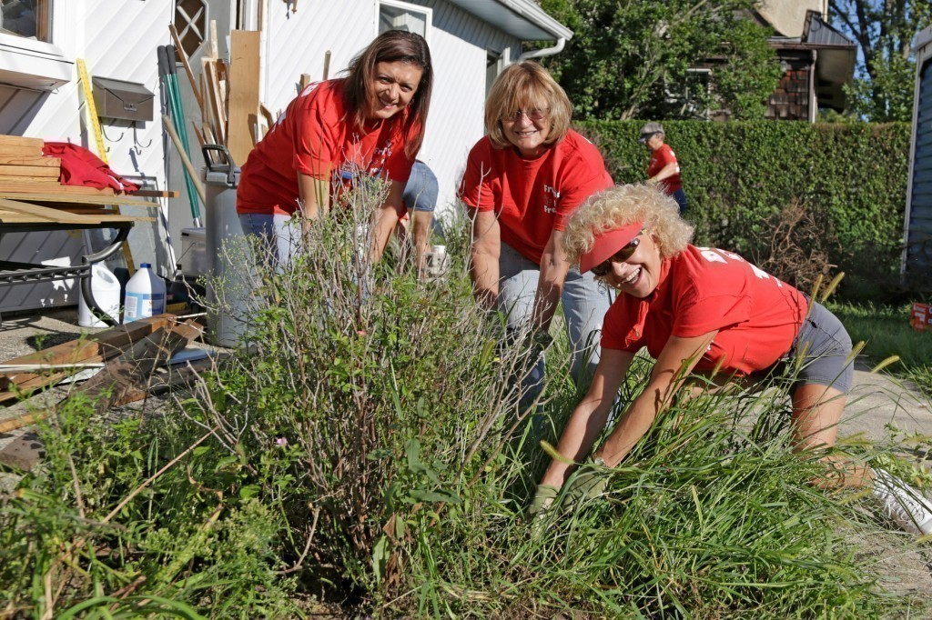 Ladies in Red: Debbie Pugliese, left, Coleen Olsen and Joan Garbo helped clear weeds from a Baldwin home that was damaged during Hurricane Sandy. The effort united Freeport and Baldwin volunteers.