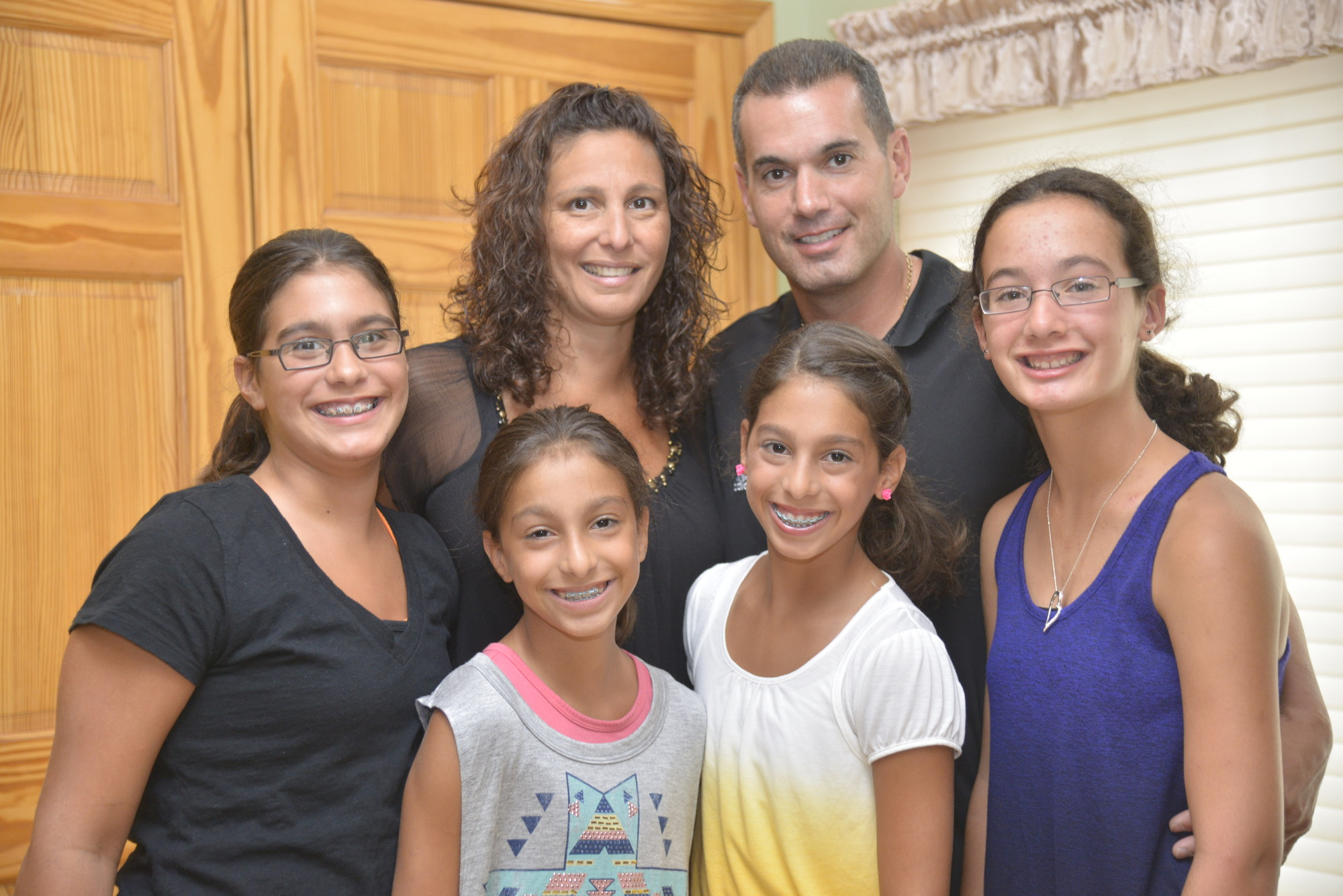 Parents Sue and Joe Cuttone with their daughters in their East Meadow home.
