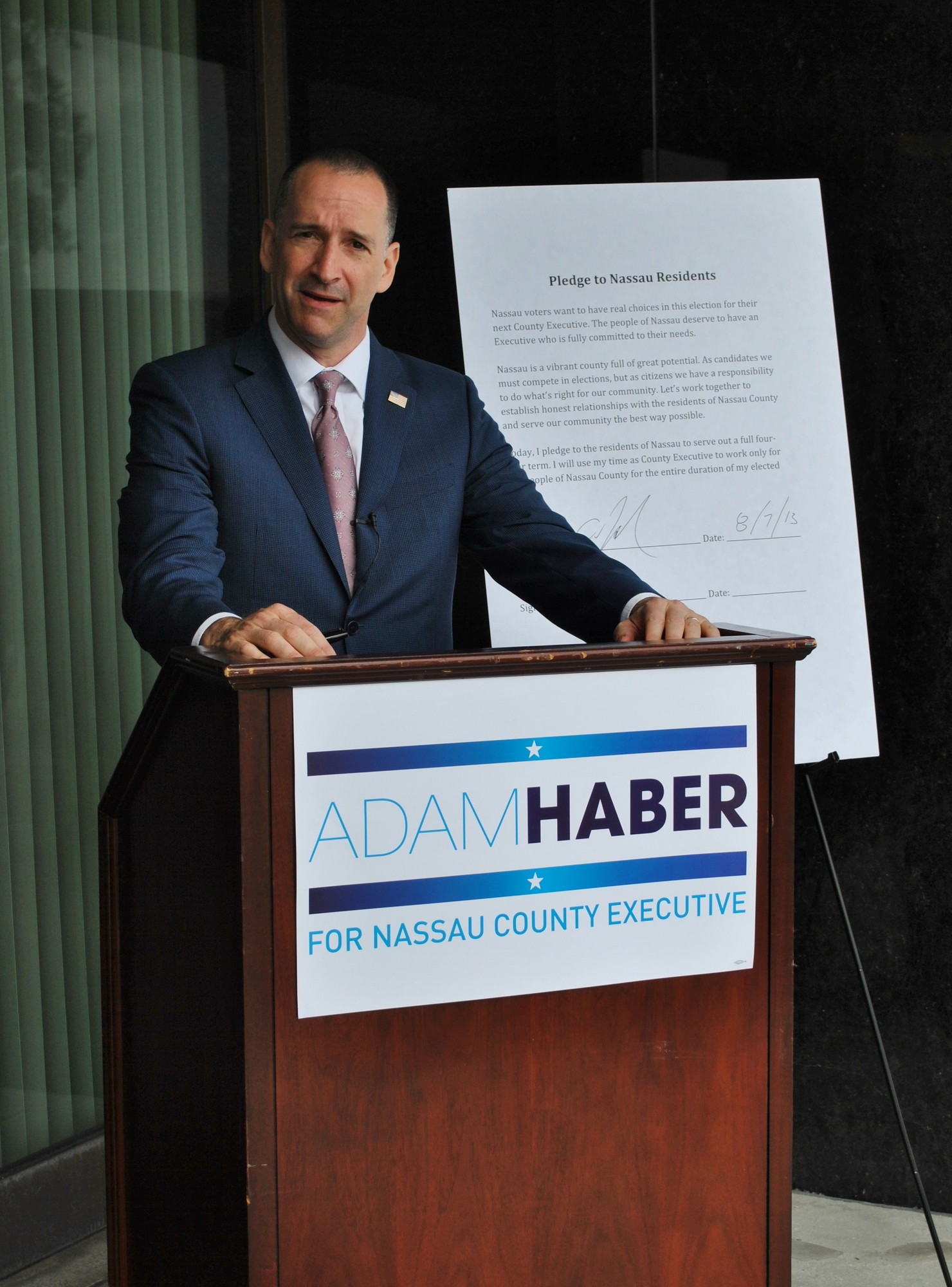 Adam Haber, speaking on the steps of the Nassau County Supreme Court building on Aug. 7, signed a pledge vowing to serve a full four-year term if elected as county executive. His is seeking the Democratic nod to run for the position.
