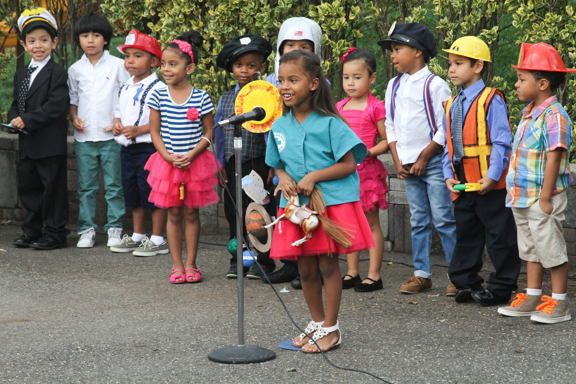 Each learning center graduate told frieds and family what they wanted to be when they grow up. From left were  Jonathan Monroy, Christian Pena, Justin Martinez, Mariah Silva, Eddie Smith, Carlos Morales, Melanie Vasquez, Joel Rodriquez, Andy Herrarte, Justin Valiente and Mia Rodriquez, at the microphone.