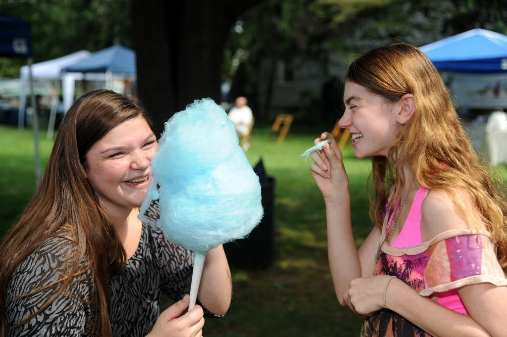 Kyra Kraus, 15, left, and Elyse Klewicki, 16, shared a laugh and some cotton candy at the Holy Trinity Orthodox Church's Faith, Food and Fellowship Festival last Saturday outside the church on Green Avenue.
