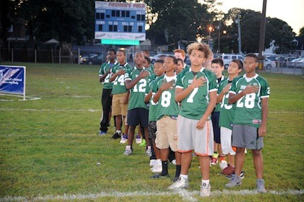 Players from the Green Hornets varsity team pause during the singing of the National Anthem at the season opening pep rally on Sept. 6 at Bob Hawkey Field.