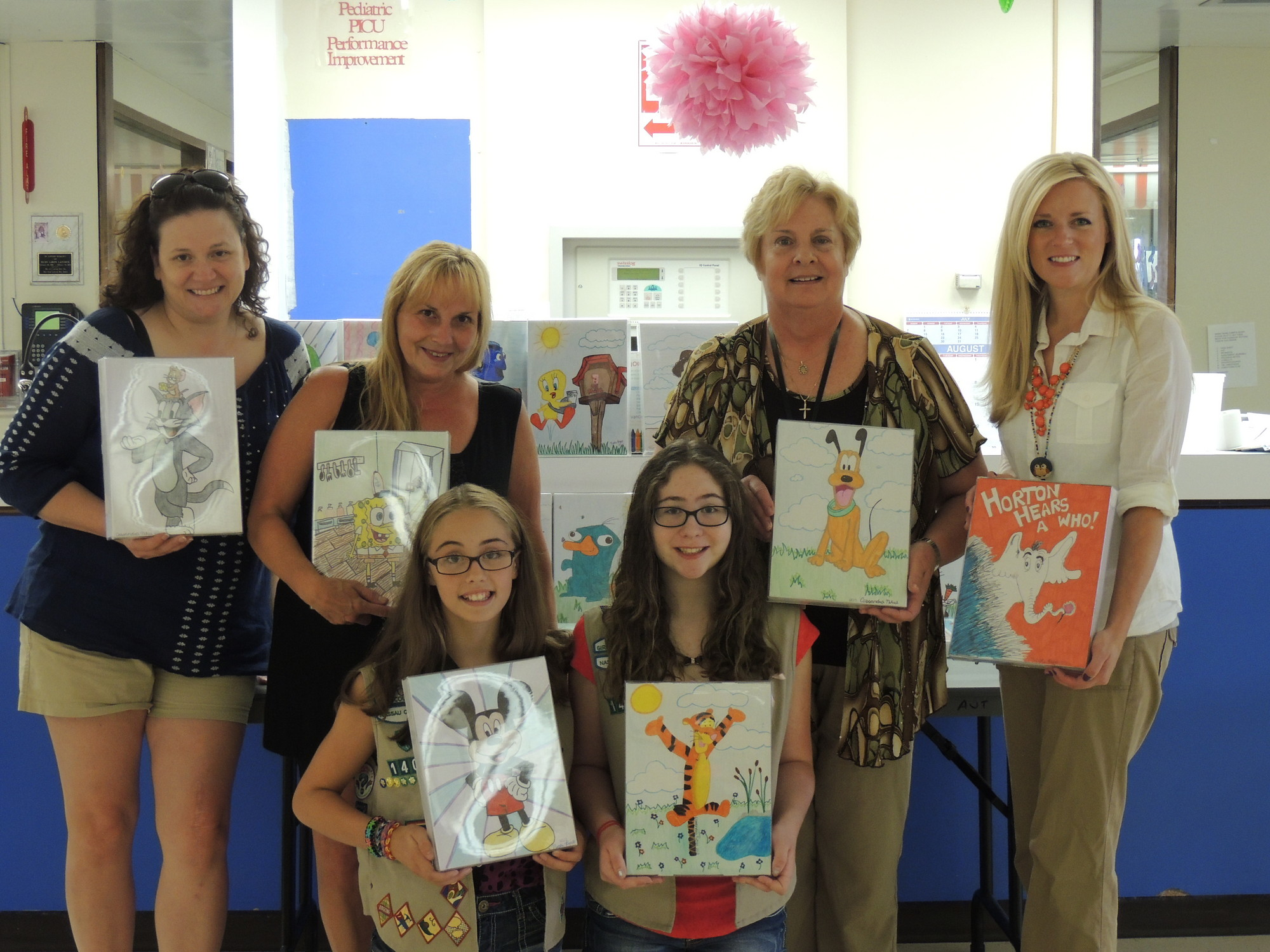 Nicole Pupo, 12, bottom left, with Cassandra Nikiel, of East Meadow Girl Scout Troop 1404, spent their summer making colorful drawings that will be hung in the pediatric ward at the Nassau University Medical Center. Behind them, from left, are troop leaders Jerri May and Tracy Pupo, NUMC pediatric nurse manager Sue Novelli and activity specialist Heather Spanfelner.